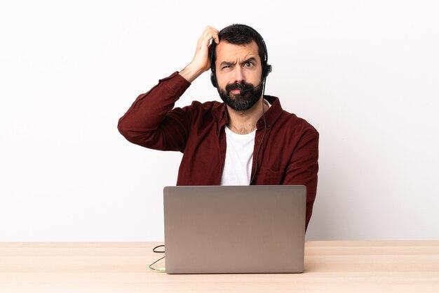Homem caucasiano do operador de telemarketing trabalhando com um fone de ouvido e um laptop com uma expressão de frustração e não compreensão.