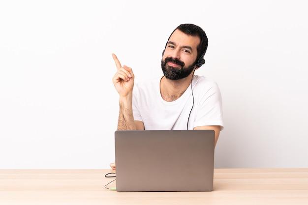 Homem caucasiano do operador de telemarketing trabalhando com um fone de ouvido e um laptop feliz e apontando para cima