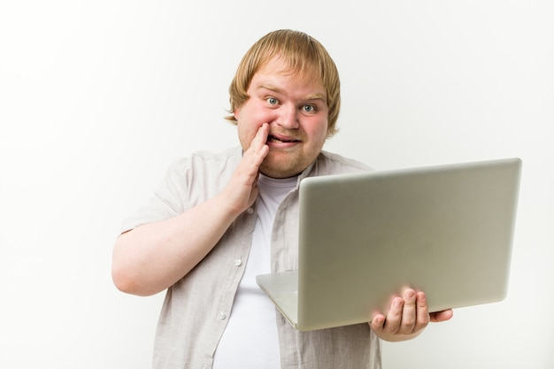Homem caucasiano do tamanho mais que prende um grito do portátil excitado para frontear.