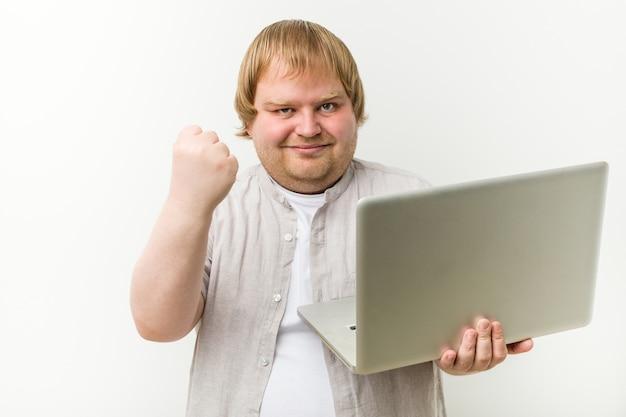 Homem caucasiano do tamanho mais que prende um portátil que mostra o punho, expressão facial agressiva.