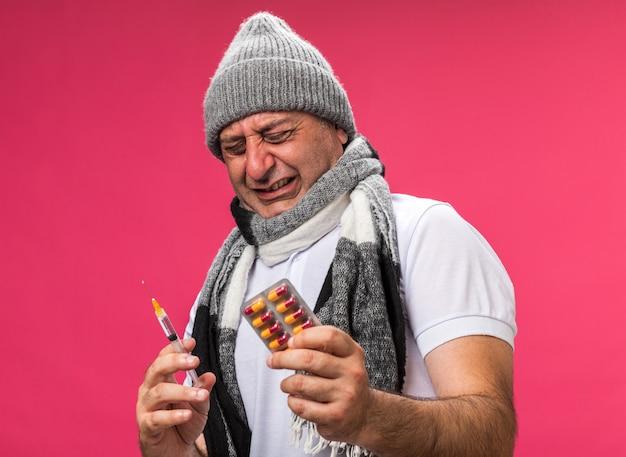 Homem caucasiano doente adulto desagradável com lenço ao redor do pescoço e chapéu de inverno com os olhos fechados segurando uma seringa e um pacote de blister de remédio isolado na parede rosa com espaço de cópia