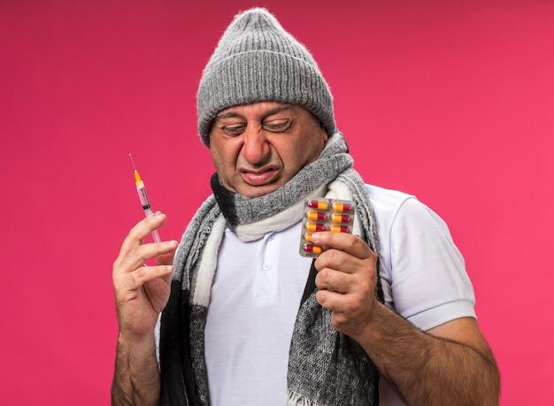 Homem caucasiano doente adulto desagradável com lenço em volta do pescoço, chapéu de inverno, segurando uma seringa e olhando para a embalagem de remédio isolada na parede rosa com espaço de cópia