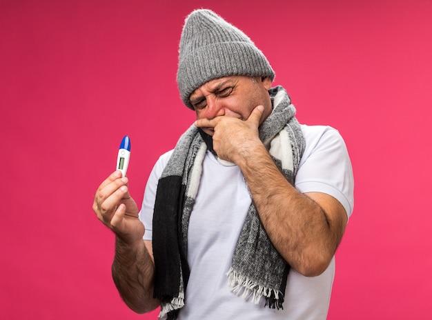 Homem caucasiano doente adulto desagradável com lenço no pescoço e chapéu de inverno coloca a mão no queixo segurando e olhando para o termômetro isolado na parede rosa com espaço de cópia