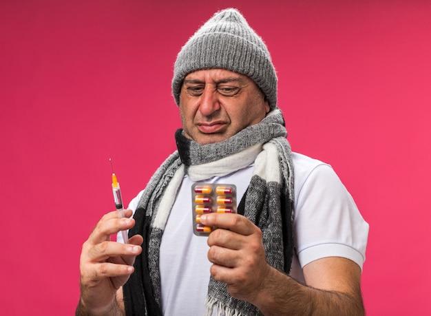 Homem caucasiano doente adulto irritado com lenço em volta do pescoço, chapéu de inverno, segurando uma seringa e olhando para a embalagem de remédio isolada na parede rosa com espaço de cópia