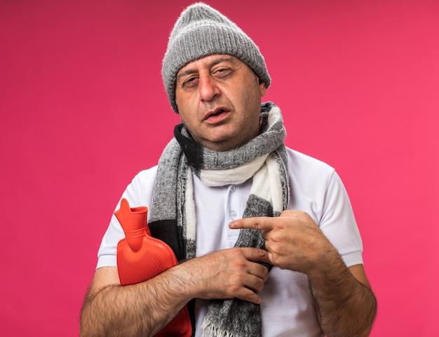 Homem caucasiano doente adulto irritado com lenço em volta do pescoço usando chapéu de inverno segurando e apontando para a garrafa de água quente isolada na parede rosa com espaço de cópia