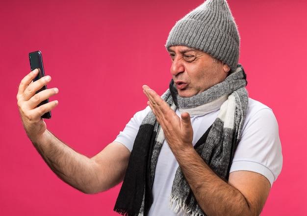 Homem caucasiano doente adulto irritado com lenço no pescoço e chapéu de inverno segurando e olhando para o telefone isolado na parede rosa com espaço de cópia