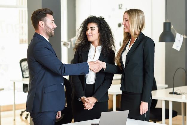 Homem caucasiano e mulher apertando as mãos vestindo terno.