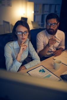 Homem caucasiano e mulher trabalhando juntos no escritório na noite