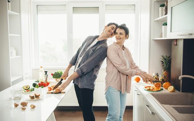 Homem caucasiano e sua esposa preparando comida na cozinha sorrindo e curtindo o tempo juntos