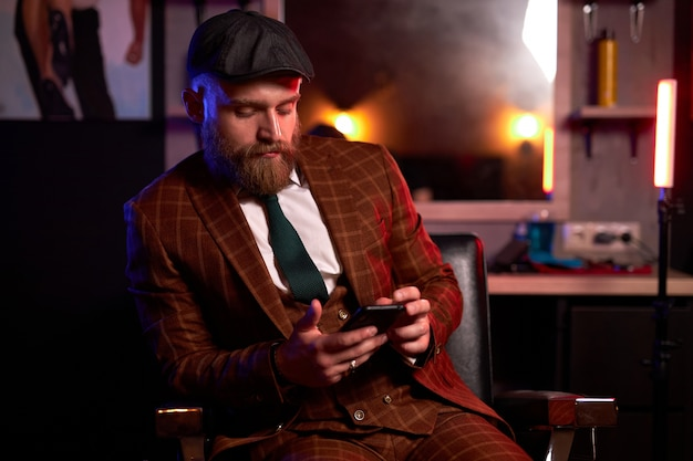 Homem caucasiano elegante em traje formal e chapéu sentado olhando para o smartphone