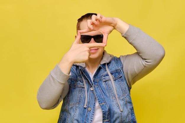 Homem caucasiano elegante em um jeans e óculos escuros sobre um fundo amarelo. as mãos mostram abstratamente um quadro do filme.