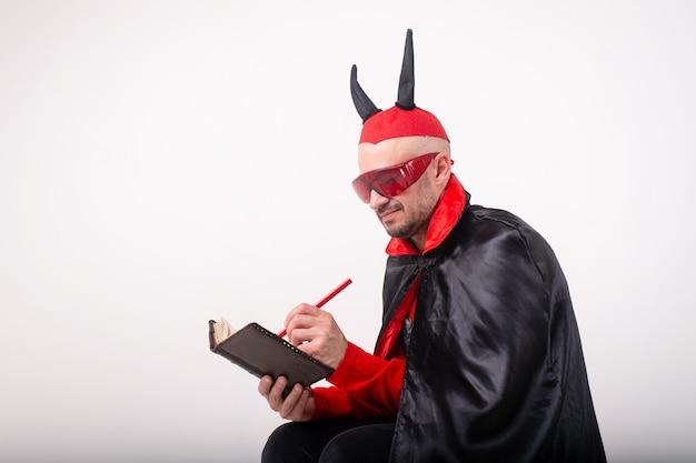 Homem caucasiano em óculos de sol vermelhos e fantasia de halloween com caneta e caderno sobre o fundo branco do estúdio.