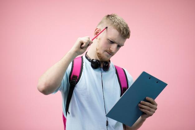 Homem caucasiano em pé digitando no tablet. caneta de exploração masculina pensativa na cabeça