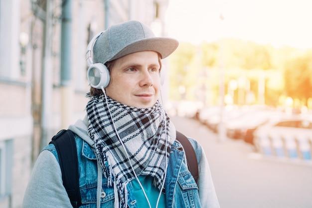 Homem caucasiano em um boné cinza ouve música em fones de ouvido