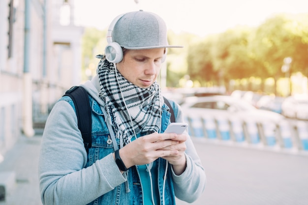Homem caucasiano em um boné cinza se comunica nas redes sociais via smartphone
