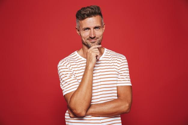Homem caucasiano em uma camiseta listrada pensando e tocando o queixo isolado no vermelho