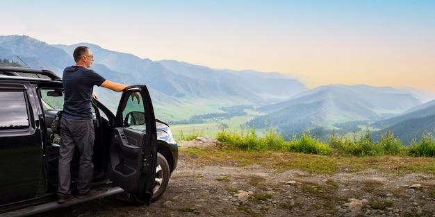 Homem caucasiano em viagem, apreciando a paisagem montanhosa ao pôr do sol. bandeira.