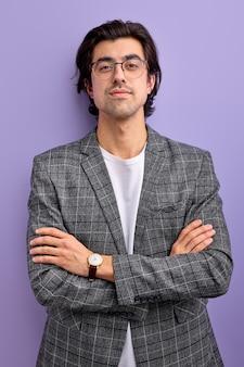 Homem caucasiano equilibrado, posando para a câmera com um terno formal, jovem do sexo masculino com roupas elegantes em pé com os braços cruzados