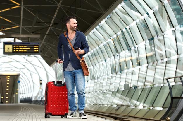 Homem caucasiano, esperando na plataforma da estação de trem