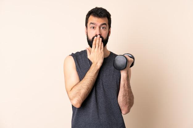 Homem caucasiano esporte com barba fazendo halterofilismo sobre parede cobrindo a boca com a mão