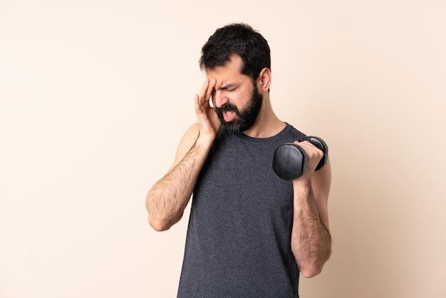 Homem caucasiano esporte com barba fazendo halterofilismo sobre parede com dor de cabeça