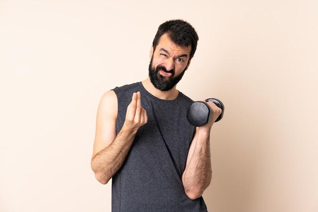 Homem caucasiano esporte com barba fazendo halterofilismo sobre parede fazendo gesto de dinheiro, mas está arruinado
