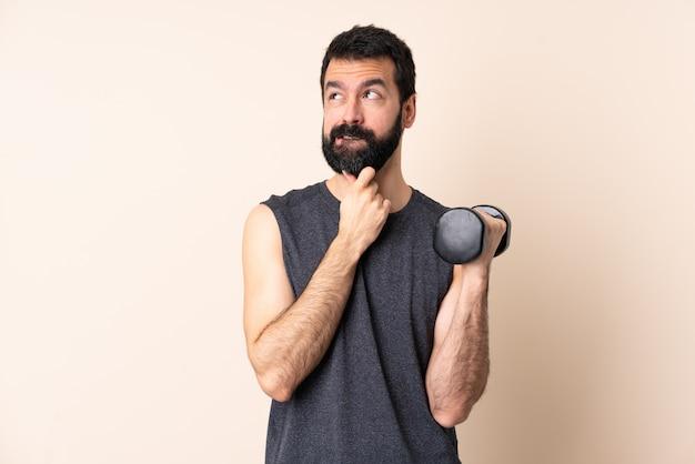 Homem caucasiano esporte com barba fazendo halterofilismo sobre parede isolada tendo dúvidas e pensando