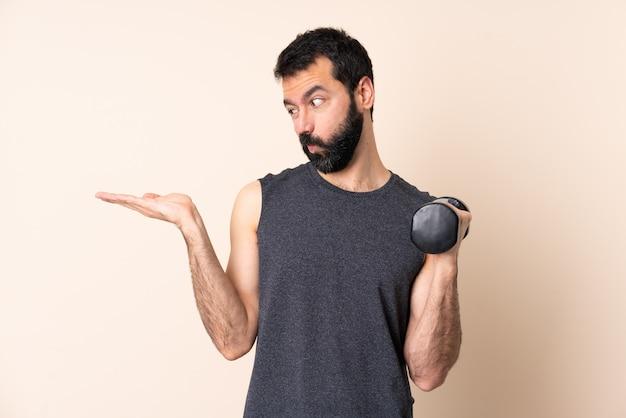 Homem caucasiano esporte com barba fazendo halterofilismo sobre parede segurando copyspace com dúvidas
