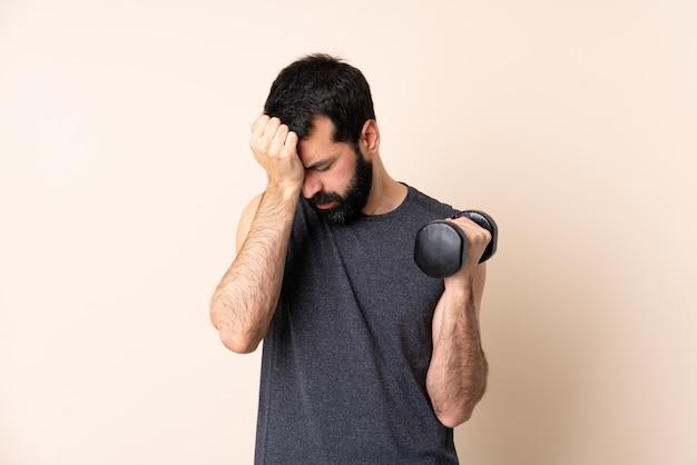 Homem caucasiano esporte com barba fazendo levantamento de peso com dor de cabeça