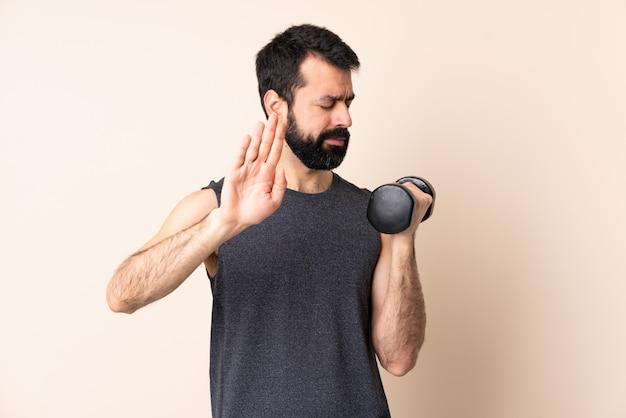 Homem caucasiano esporte com barba fazendo levantamento de peso isolado fazendo gesto de parada e decepcionado