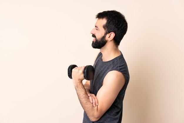 Homem caucasiano esporte com barba fazendo levantamento de peso na posição lateral