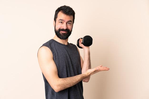 Homem caucasiano esporte com barba fazendo levantamento de peso sobre a parede, apresentando uma idéia enquanto olha sorrindo para