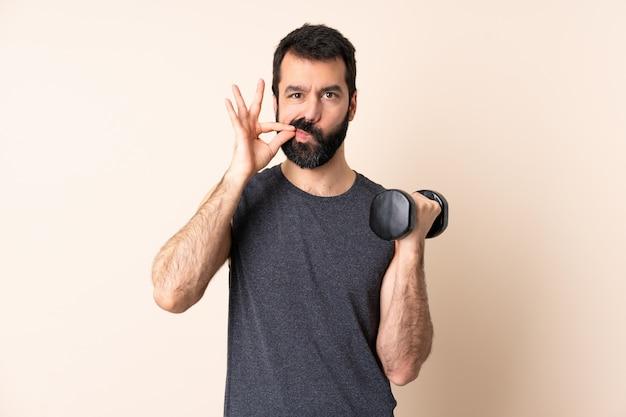 Homem caucasiano esporte com barba fazendo levantamento de peso sobre a parede, mostrando um sinal de gesto de silêncio