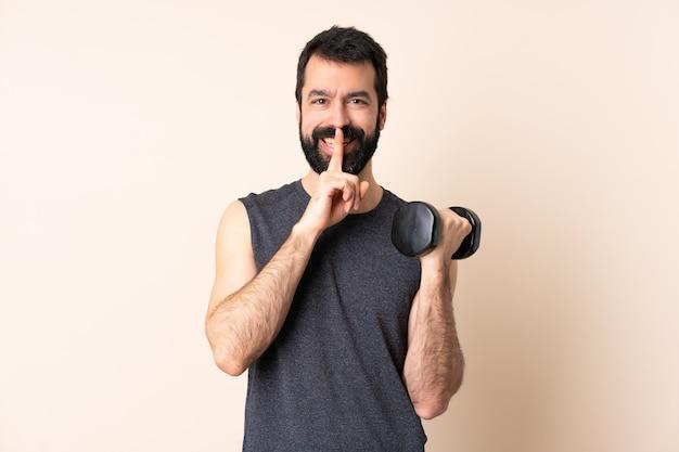 Homem caucasiano esporte com barba fazendo levantamento de peso sobre a parede, mostrando um sinal de silêncio gesto com o dedo na boca