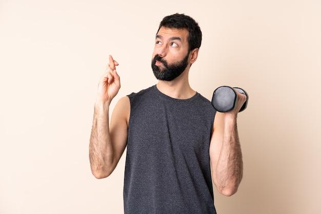 Homem caucasiano esporte com barba fazendo levantamento de peso sobre o espaço isolado, com os dedos cruzando e desejando o melhor