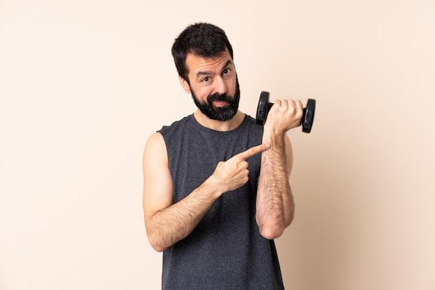 Homem caucasiano esporte com barba fazendo levantamento de peso sobre o espaço isolado, fazendo o gesto de chegar atrasado