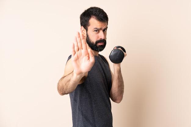 Homem caucasiano esporte com barba fazendo levantamento de peso sobre parede, fazendo o gesto de parada e decepcionado