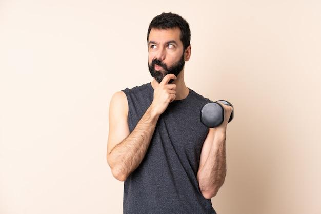 Homem caucasiano esporte com barba fazendo levantamento de peso sobre parede isolada com dúvidas e com a expressão do rosto confuso
