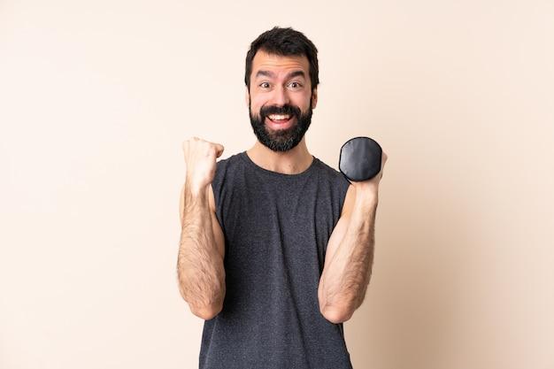 Homem caucasiano esporte com barba fazendo levantamento de peso sobre parede isolada comemorando uma vitória na posição de vencedor