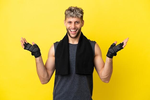 Homem caucasiano esportivo isolado em um fundo amarelo com expressão facial chocada