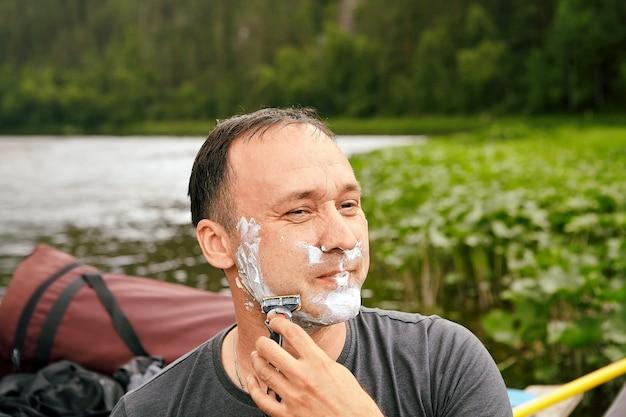 Homem caucasiano está barbeando o rosto com a ajuda de espuma e lâmina de barbear na manhã perto do rio durante suas férias.