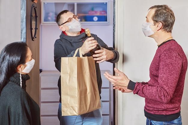 Homem caucasiano está dando um presente para seus amigos durante o isolamento doméstico em um período de pandemia de coronavírus