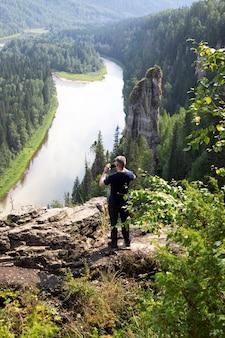 Homem caucasiano está de costas viradas, fazendo uma foto de paisagem de pilares usvinskie com dedos de demônios