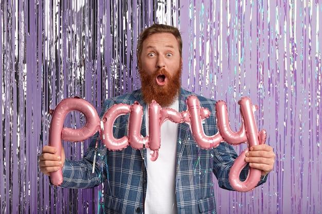 Homem caucasiano estupefato com espessa barba ruiva, surpreso ao ver tantos visitantes na festa de despedida, carrega balões em forma de carta, vestido com roupas formais, encostado na parede decorada