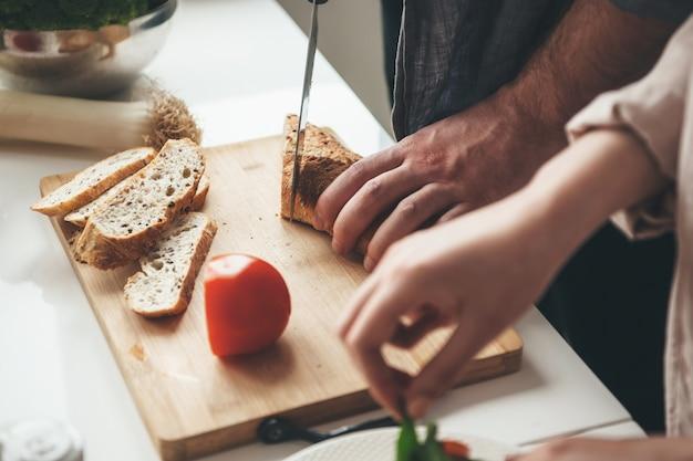 Homem caucasiano fatiando pão enquanto a esposa está preparando uma salada de legumes na cozinha