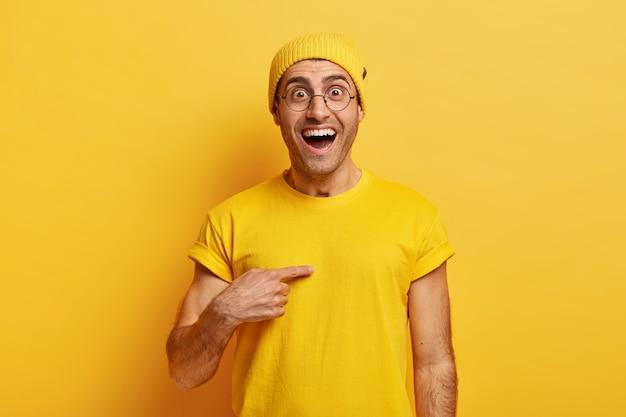 Homem caucasiano feliz aponta feliz para si mesmo, se surpreende com olhar alegre, pergunta se exatamente ele ganhou a competição