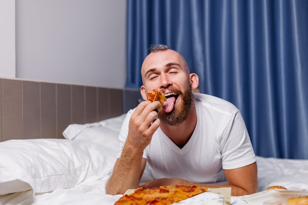 Homem caucasiano feliz comendo fast food em casa, no quarto na cama. o homem pediu comida online para levar e comeu pizza e hambúrgueres no quarto confortável