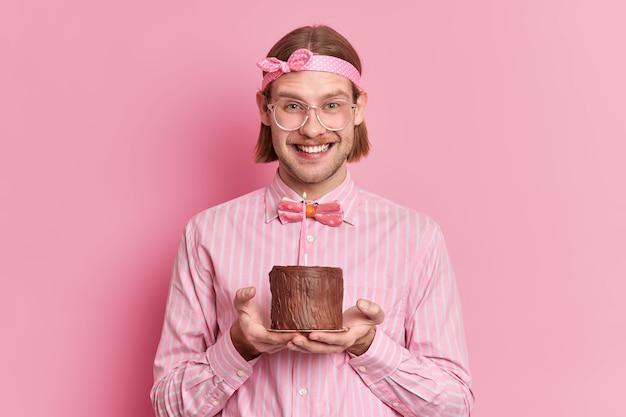Homem caucasiano feliz que vai comemorar o aniversário, sorri e usa uma camisa com tiara e gravata borboleta segura um bolo de chocolate com uma vela acesa isolada sobre a parede rosa