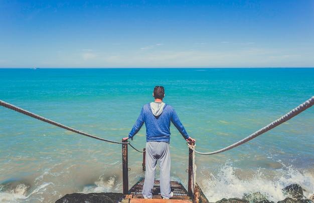 Homem caucasiano fica na escada de madeira velha descendo para o mar mediterrâneo