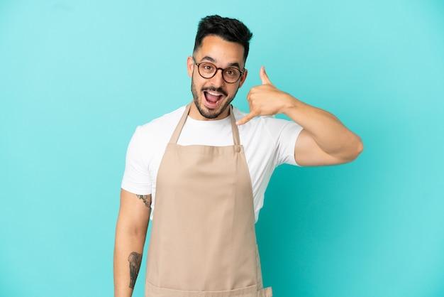Homem caucasiano garçom de restaurante isolado em um fundo azul, fazendo gesto de telefone. ligue-me de volta sinal